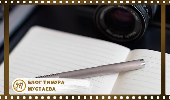 фотоаппарат на столе с тетраткой