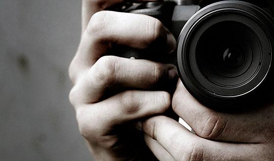 в руке с фотоаппаратом