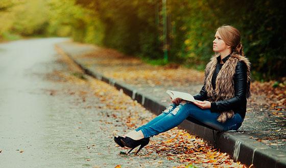 девушка сидит с книгой в пасмурный день