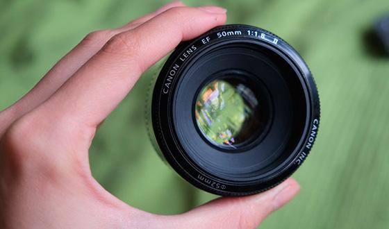 объектив кэнон 50 мм 1.8 в руке
